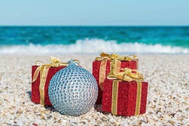 Weihnachtsdekoration und ball auf dem sand eines strandes
