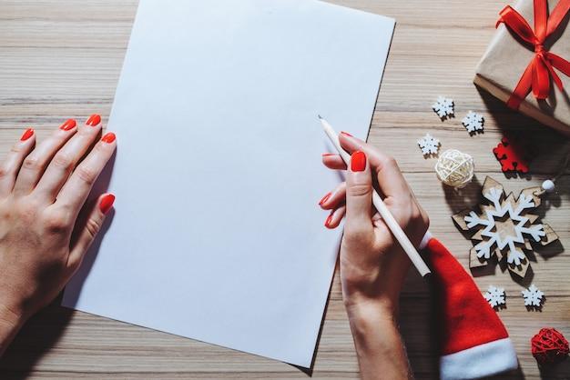 Weihnachtsdekoration und geschenkbox auf holzschreibtisch. weibliche hände, die bleistift halten, schreiben beste wünsche auf das leere weiße stück papier
