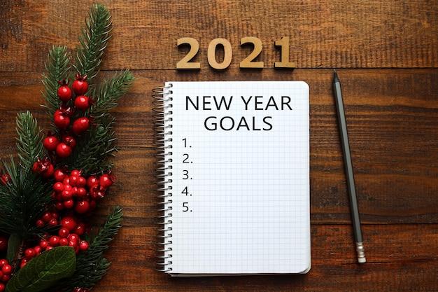 Weihnachtsdekoration und leeres notizbuch zum schreiben von zielen