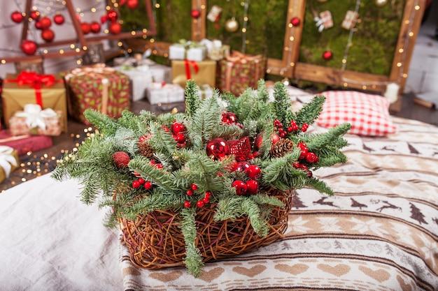 Weihnachtsdekoration. weihnachtskorb mit tannenzweigen und roten kugeln