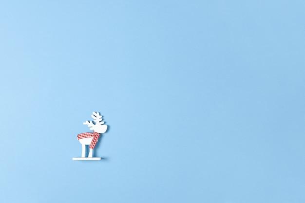 Weihnachtsdekoration, weiße rotwild des spielzeugs im karierten schal auf blauem pastellhintergrund mit copyspace. festlich, neujahr.