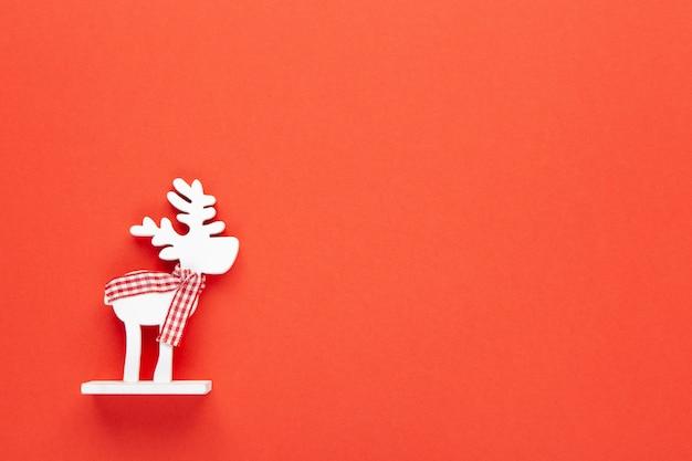 Weihnachtsdekoration, weiße rotwild des spielzeugs im karierten schal auf rotem hintergrund mit kopienraum