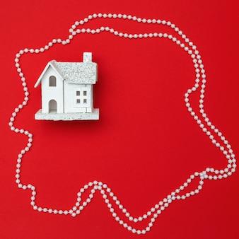 Weihnachtsdekoration, weißes holzhaus auf rotem papierhintergrund. weihnachten flach liegen. minimales konzept des neuen jahres.
