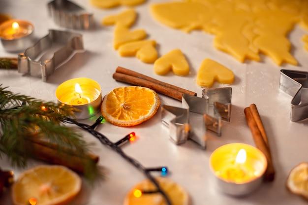 Weihnachtsdekorationen auf dem tisch in der nähe von flach geschnittenem teig, der zum backen bereit ist