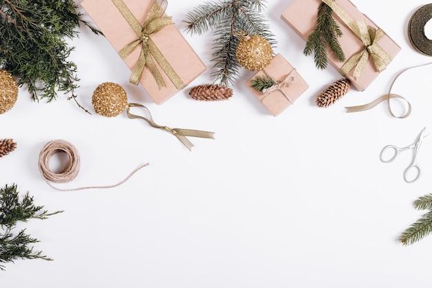 Weihnachtsdekorationen auf einem weißen hintergrund: niederlassungen der tanne, geschenkboxen, bänder, spielwaren, seil, scheren