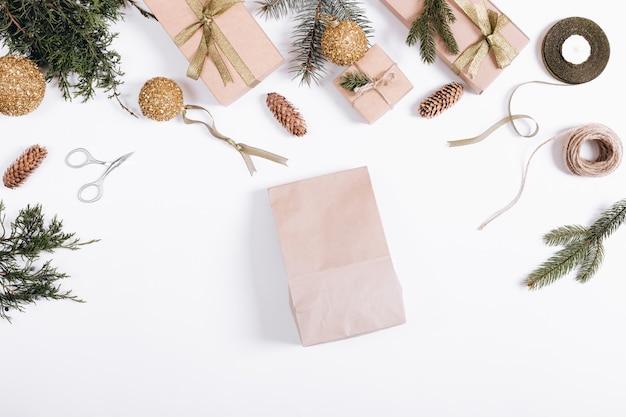 Weihnachtsdekorationen auf einem weißen hintergrund: papiertüte, tannenzweige, geschenkboxen, bänder, spielwaren, seil, scheren