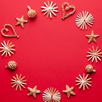 Weihnachtsdekorationen aus natürlichem holz auf rotem hintergrund, exemplar. flache lage, weihnachtskarte mit ornamenten aus ökologischen materialien, draufsicht