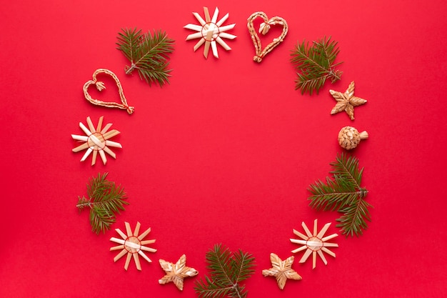 Weihnachtsdekorationen aus natürlichem holz und kiefernrahmen auf rotem hintergrund, kopienraum. flache lage, weihnachtskarte mit ornamenten aus ökologischen materialien, draufsicht