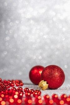 Weihnachtsdekorationen aus roter kugel auf unscharfem glitzerhintergrund, kopienraum