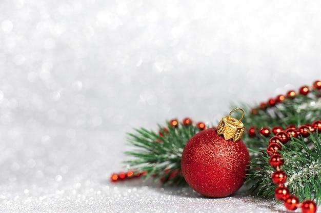 Weihnachtsdekorationen aus roter kugel mit ästen auf unscharfem glitzerhintergrund, kopienraum