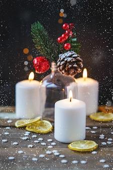 Weihnachtsdekorationen, brennende kerzen, schneeflocken, süßigkeit, zitrusfrucht, fichte auf einem hölzernen hintergrund. neujahrs . postkarte