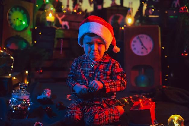 Weihnachtsdekorationen. ein frustrierter junge sitzt auf dem boden.