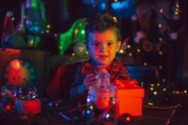 Weihnachtsdekorationen. ein süßer junge sitzt an einem tisch mit weihnachtsspielzeug und geschenken. postkarte.