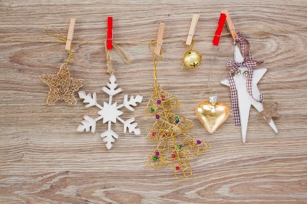 Weihnachtsdekorationen hängen am seil auf hölzernem hintergrund