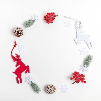 Weihnachtsdekorationen hirsch, tannenzweige, rote beeren, schneeflocken im kreis auf weißem hintergrund angeordnet