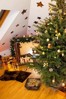 Weihnachtsdekorationen im studio, im großen natürlichen tannenbaum mit goldenen bällen, in den bögen und in den schneeflocken, im hölzernen kamin und in den kerzen