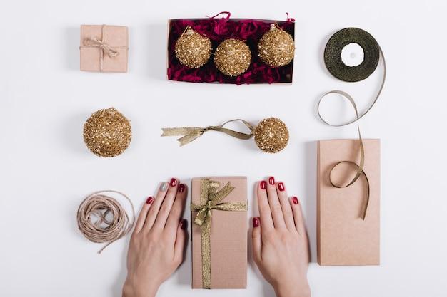 Weihnachtsdekorationen, kästen mit geschenken und die hände der frauen