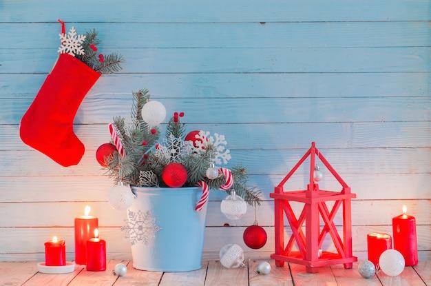 Weihnachtsdekorationen mit brennenden kerzen auf blauem hölzernem hintergrund