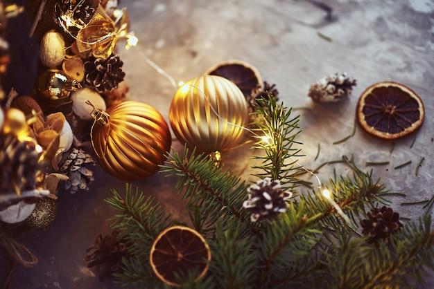 Weihnachtsdekorationen mit goldenen bällen, tannenbaumast und girlandenlichtern auf dunkelheit