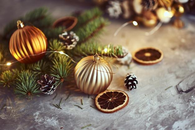 Weihnachtsdekorationen mit goldenen bällen, tannenbaumast und girlandenlichtern