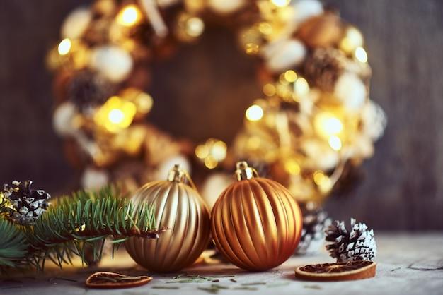 Weihnachtsdekorationen mit goldenen bällen und girlandenlichtern auf einem dunklen hintergrund