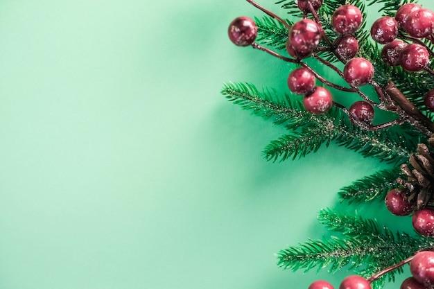 Weihnachtsdekorationen mit roten beeren und tannenzweigen auf einem schönen tadellosen hintergrund.
