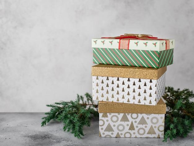 Weihnachtsdekorationen mit verschiedenen bunten geschenkboxen, weihnachtsbaumaste. grauen hintergrund, kopie, raum
