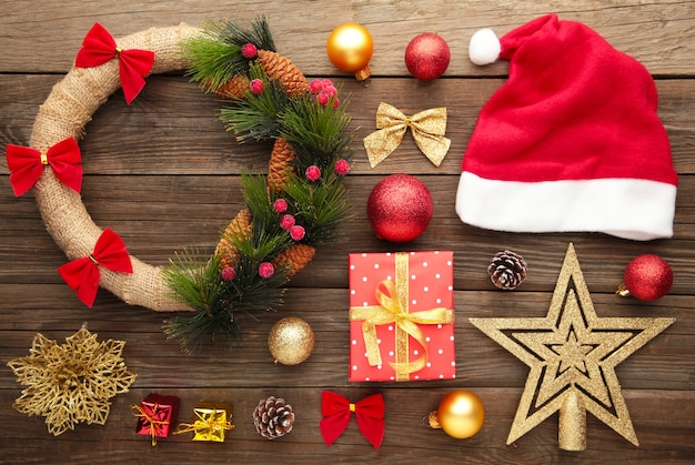 Weihnachtsdekorationen mit weihnachtsmütze und kranz auf grauem hintergrund. draufsicht