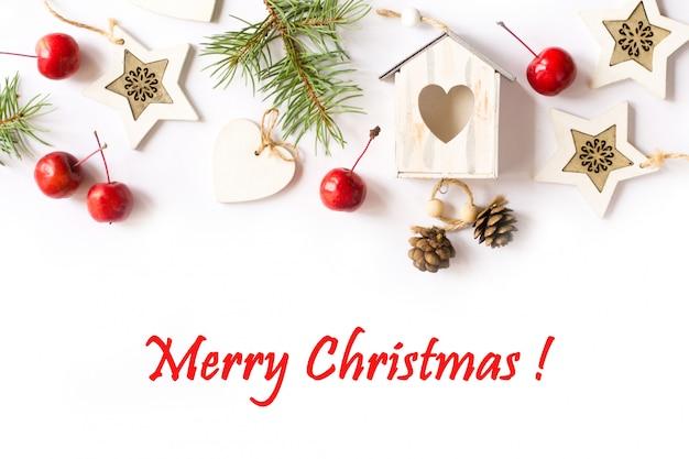 Weihnachtsdekorationen, tannenbaumaste, rote äpfel auf weißem hintergrund