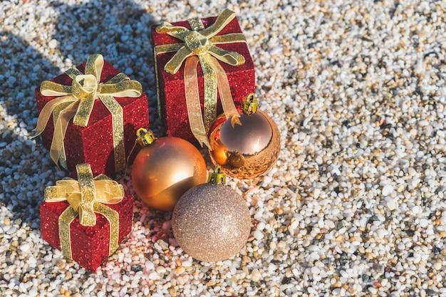Weihnachtsdekorationen und bälle auf dem sand eines strandes