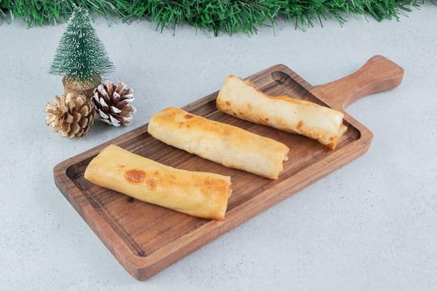 Weihnachtsdekorationen und ein tablett mit pfannkuchen auf marmorhintergrund.