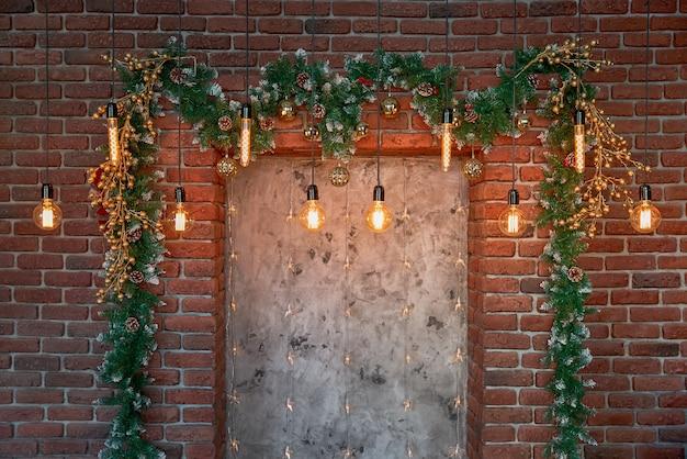 Weihnachtsdekorationen und eine girlande von lampen auf einer backsteinmauer