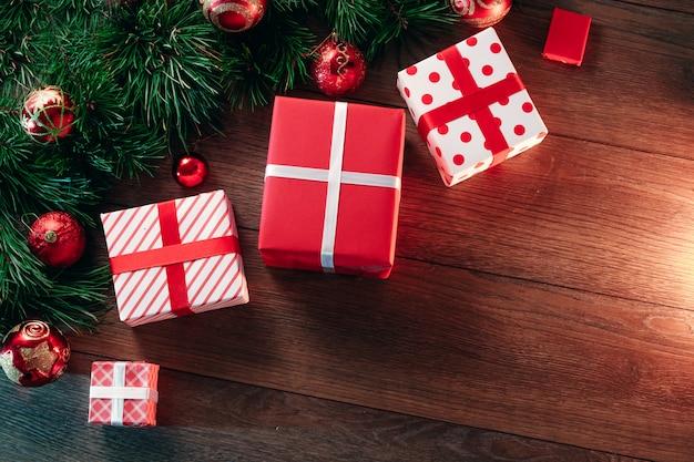 Weihnachtsdekorationen und geschenke, kiefernniederlassungen auf einem holztisch. feiertage weihnachten. copyspace. sicht von oben.