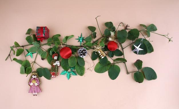 Weihnachtsdekorationen und -reben mit hellgelbem hintergrund.