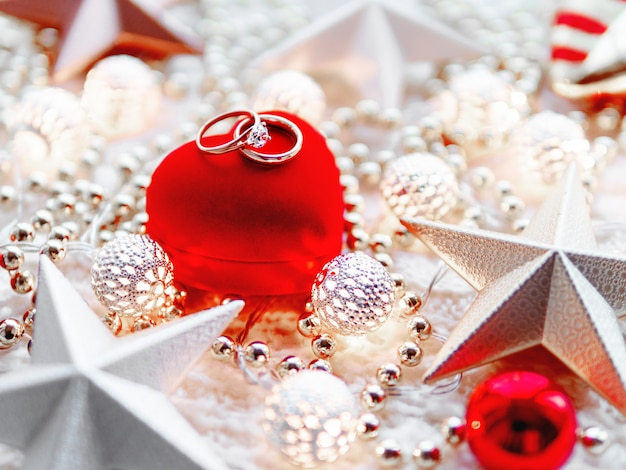 Weihnachtsdekorationen und rote herzgeschenkbox mit hochzeitsdiamantringen