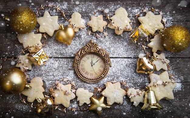 Weihnachtsdekorationen und weihnachtsplätzchen mit dem schnee und der uhr auf dem tisch