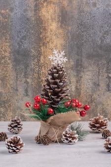 Weihnachtsdekorationen von stechpalmenbeeren und tannenzapfen auf weißem tisch.