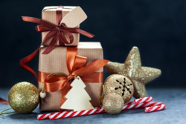 Weihnachtsdekorationen. zwei geschenke verpacktes handwerk mit feiertagsdekoration auf dunkelgrauem hintergrund.