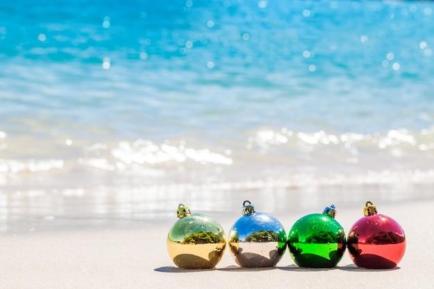 Weihnachtsdekorationsbälle auf seeküste mit weißem sand und blauem wasser
