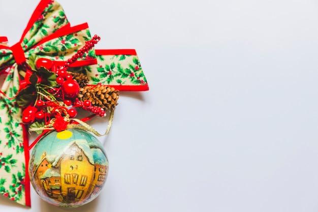 Weihnachtsdekorationsflitter mit heiliger beere; kegel und band auf weißem hintergrund