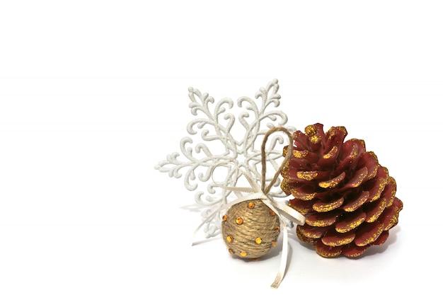 Weihnachtsdekorationskiefernkegel mit scheinen, glänzender schneeflocke und handgemachter kugel auf weißem b