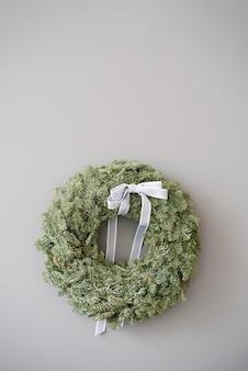 Weihnachtsdekorationskranz mit einer grauen schleife an der wand einer grauen betonwand mit einem kopierraum