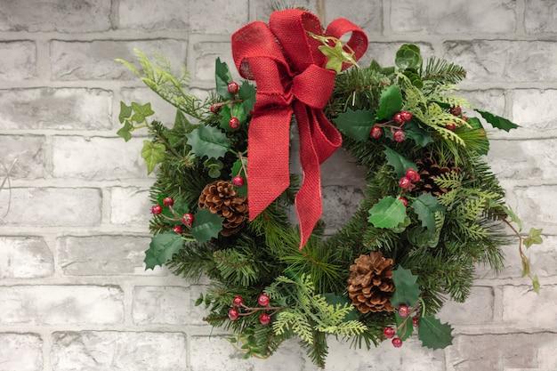 Weihnachtsdekorationskranz mit roten stechpalmenbeeren, tannenzapfen und rotem band beugen auf backsteinmauer