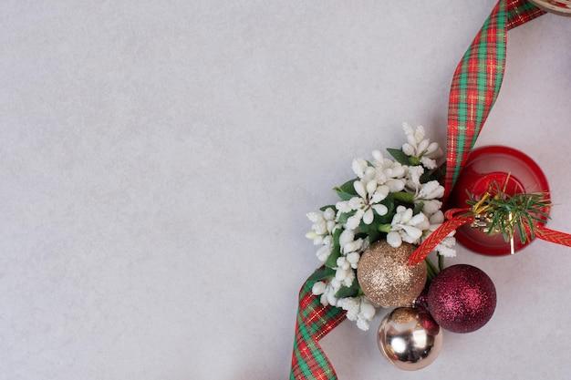 Weihnachtsdekorationskugeln mit band auf weißem tisch.