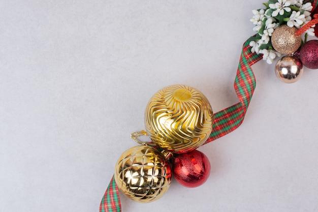 Weihnachtsdekorationskugeln mit band auf weißer oberfläche