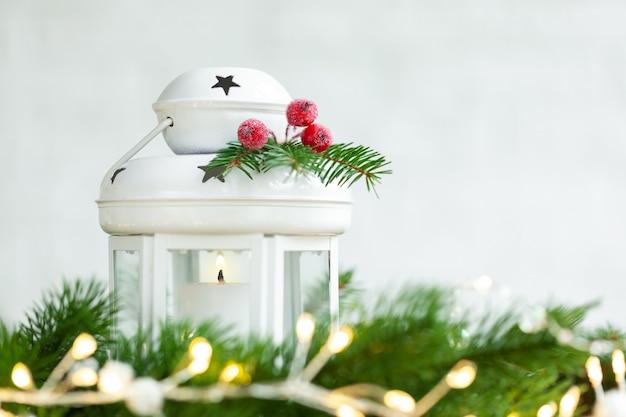 Weihnachtsdekorationslaterne mit brennender kerze und weihnachtskugeln auf hellem festlichem hintergrund.