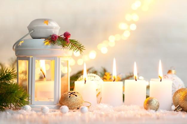 Weihnachtsdekorationslaterne mit einer kerze und vier brennenden kerzenlichtern am heiligabend. hintergrund mit festlichen bokeh-lichtern und platz für ihren text.