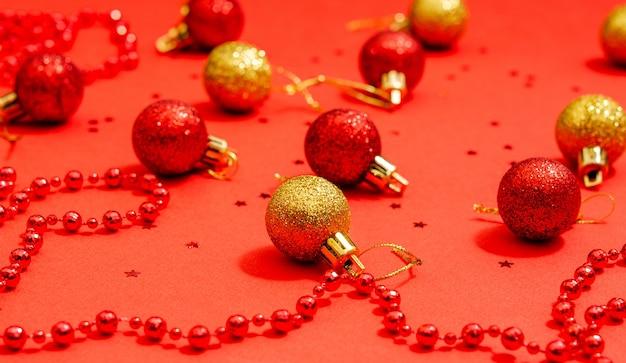 Weihnachtsdekorationsspielzeug in roter und goldener farbe mit roten perlen für dekor und sterne auf einer roten oberfläche. platz für kopierraum, flach legen. urlaubskonzept. nahansicht