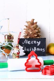 Weihnachtsdekorationswerkzeuge für das backen von plätzchen bilden ein nudelholz auf einer rustikalen art der hellen hölzernen hintergrundselektiven weichzeichnung