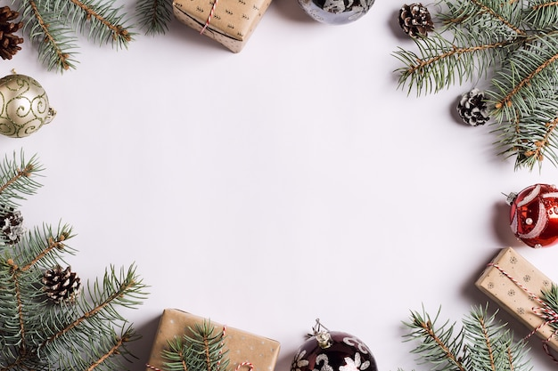 Weihnachtsdekorationszusammensetzungsgeschenkboxkiefernkegelball-fichtenzweige auf weißer festlicher tabelle